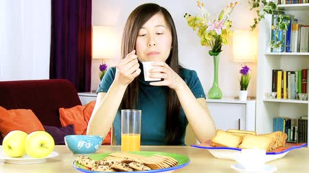 йогурт : Asian woman at home eating white yogurt medium shot Стоковые видеозаписи
