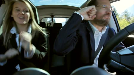 vzrušený : Cool man and woman in business suit driving car dancing