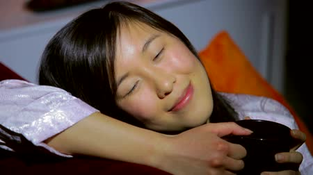 içme : Happy Chinese American woman having good time at home on the couch Stok Video