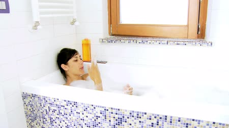 foam bath : Happy woman relaxing in bath tub wide shot Stock Footage