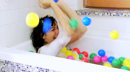 foam bath : Flying colored bubble falling on woman in bath tub slow motion