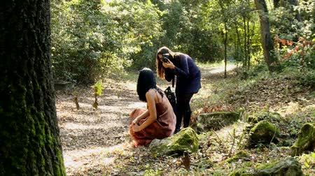 fényképész : Woman photographer in action in the forest with female model