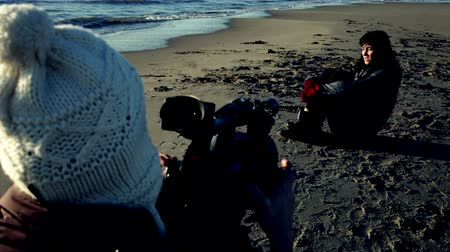 atirar : Woman with camera shooting model on the beach Stock Footage