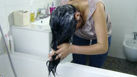 чистый : Young woman putting shampoo on hair at home Стоковые видеозаписи