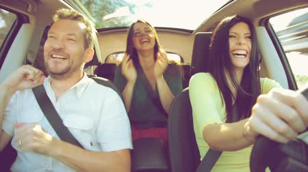 távozás : Beautiful happy people dancing in car while going in vacation