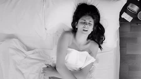 cramps : Black and white portrait of woman in bed ill with stomach ache
