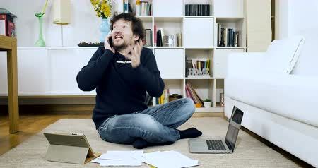 impostos : Man at home on the phone with accountant desperate about taxes Stock Footage