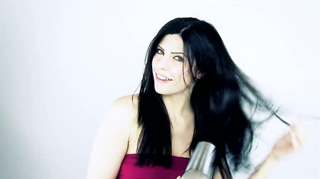 darbe : Beautiful female model blow drying long hair smiling looking camera isolated. Stok Video