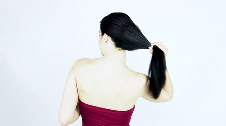 undo : Woman with long silky black hair undoing ponytail smiling looking camera