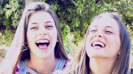 смеющийся : Closeup of two happy girls laughing