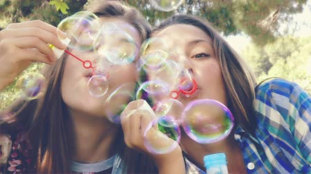 darbe : Happy teenagers having fun in park with bubbles closeup
