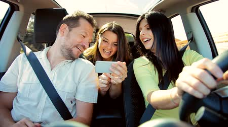 текст : Friends having fun in car with smartphone driving in summer Стоковые видеозаписи
