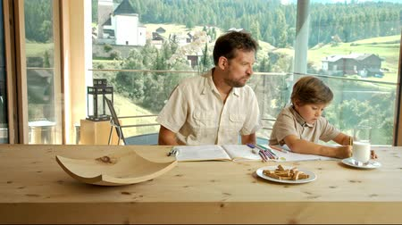 домашнее задание : Father helping little boy doing homework at home in the mountains travelling shot