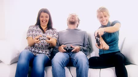 oynamak : Two women and one man playing videogame with console