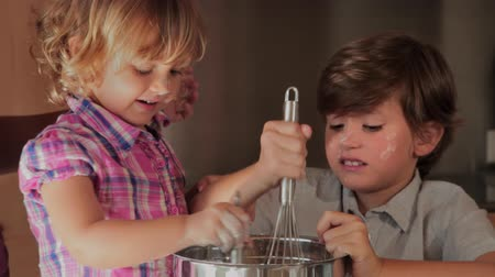 keksz : children cooking a cake helped by the mother at home