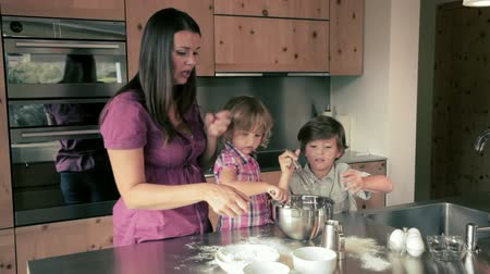 keksz : mother making a cake with her sons in kitchen