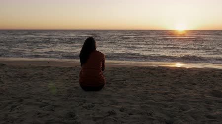 lonely : Sad lonely woman looking sunset in front of ocean dolly shot