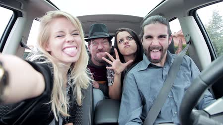 друзья : Cool people having fun laughing in car while taking selfie