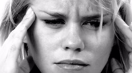 zihinsel : Sad blond woman at home sitting on sofa with strong headache tired black and white closeup