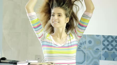 undo : Happy beautiful woman in front of mirror in the morning undoing ponytail look