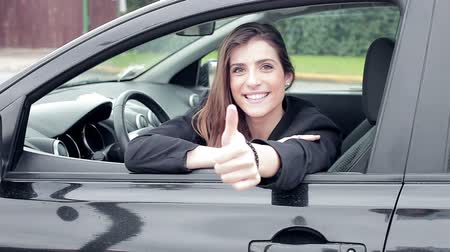 engedély : Beautiful woman looking camera smiling thumb up from window of black car