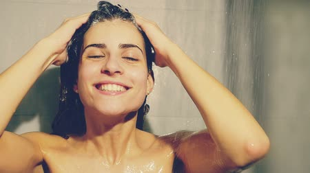 şampuan : Cute woman washing hair with shampoo making funny faces under shower
