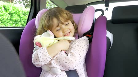 carseat : Beautiful blond baby girl sitting in car hugging plush toy looking amended Room