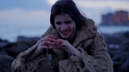 zdjęcia seryjne : Woman crying covered with blood sitting on rocks in front of ocean looking her hands slow motion