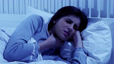 doente : Woman ill in bed at night feeling sick throat Stock Footage