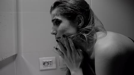 megrémült : Woman with strong makeup washing face crying desperate slow motion black and white