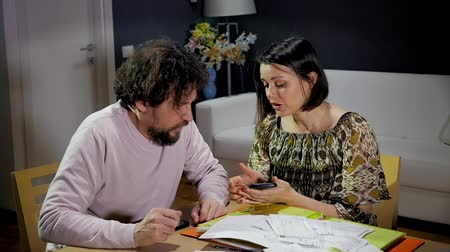 calculadora : Unhappy couple calculating bills at home