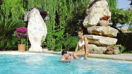 джакузи : Happy couple splashing in pool having fun with water Стоковые видеозаписи