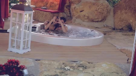 джакузи : Happy couple in jacuzzi in outdoor spa doing heart with hands