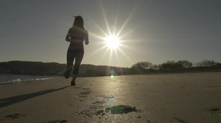kum saati : Girl running in back light near the sea and the sun in the background Stok Video