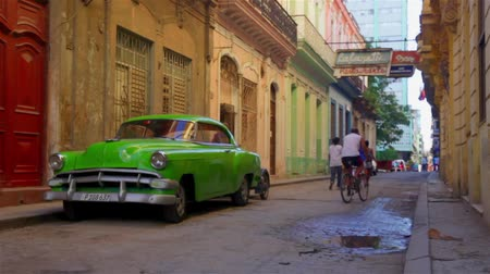 kübalı : Vintage green car parked in the Habana Vieja district with people walking around Stok Video