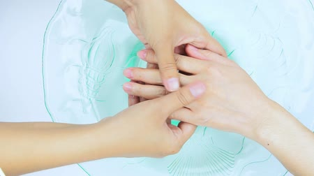 tırnak : Hand massage process before nail polish or hand spa in nail salon and spa shop. Hand dip in water in glass bowl. Hand treatment by worker in beauty shop. Woman in first step process of manicure. Stok Video