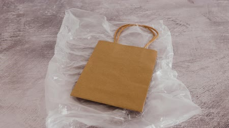 biodegradable : sustainable materials and packaging, paper shopping bag landing on top of plastic bag