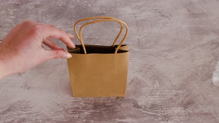 biodegradable : sustainable materials and packaging, hand throwing plastic bag out of the screen replacing it with paper shopping bag