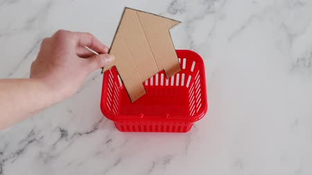 assess : home buying and property investment concept, hand placing miniature cardboard house into shopping cart