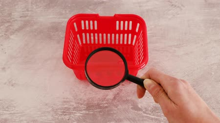 assess : market research concept, hand analyzing shopping basket with magnifying glass metaphor of researches about customer spending habits and feedback