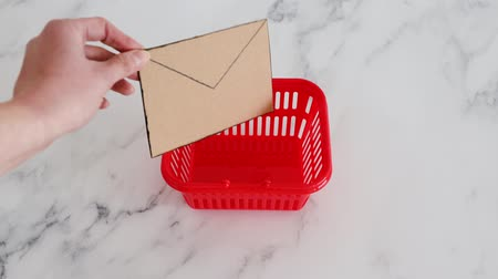 liste : promotional newsletter and mailing list concept, hand placing email envelope miniature icon made of cardboard in shopping basket Stok Video