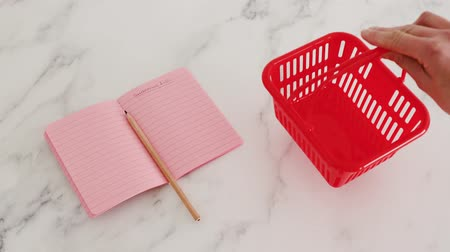 papeteria : planning and budgeting for your shopping concept, hand placing shopping basket next to notebook with shopping list