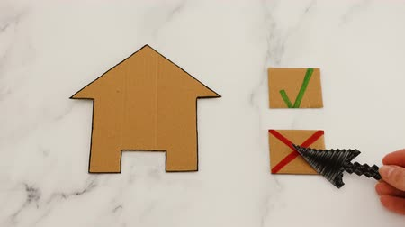 assess : choosing a new house to rent of buy concept, hand placing cursor icon on No option with cross next to miniature cardboard house