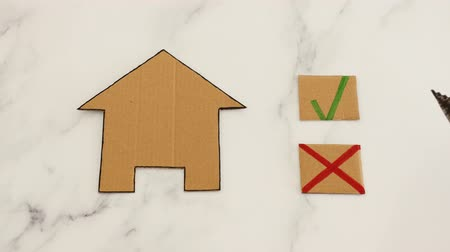 assess : choosing a new house to rent of buy concept, hand placing cursor icon on green tick next to miniature cardboard house