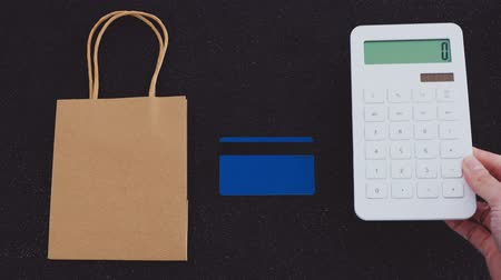 nagyító : concept of shopping budget and spending habits, calculator placed next to paper shopping bag and credit card on desk
