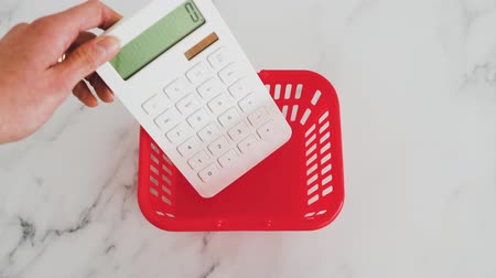 nagyító : concept of shopping budget and spending habits, hand placing calculator and magnifying glass into shopping basket
