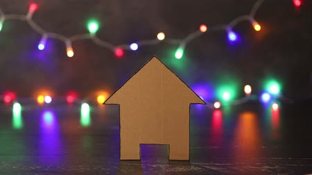 assess : concept of moving or buying a new house, miniature cardboard house placed in front of multicolor string lights bokeh going on and off Stock Footage