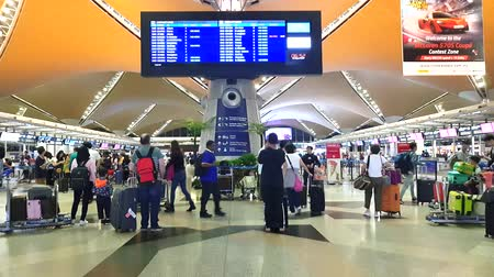 KUALA LUMPUR INTERNATIONAL AIRPORT - AUGUST 18, 2019: People passing by at the flight departure information timetable Stock Footage