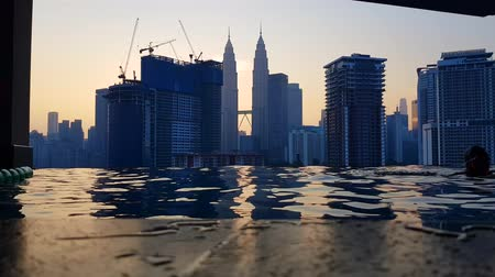 KUALA LUMPUR, MALAYSIA - JANUARY 26, 2020: 4k UHD footage of tourist swimming at rooftop pool and building in Kuala Lumpur, Malaysia during sunrise