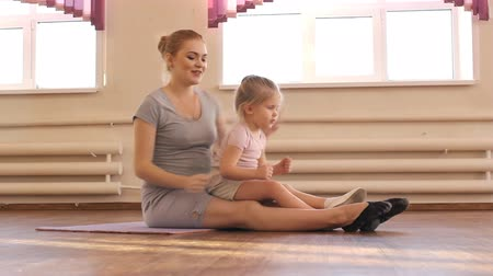 мама : Pregnant woman with her first kid daughter doing gymnastics
